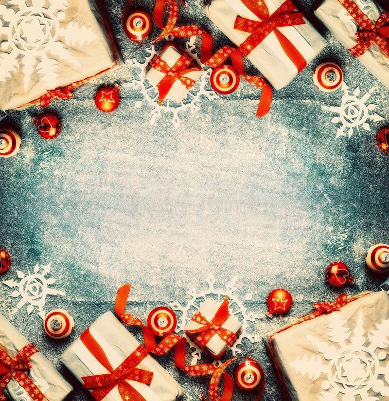 与礼物盒、红色欢乐假日装饰和纸雪花的圣诞节背景 库存照片
