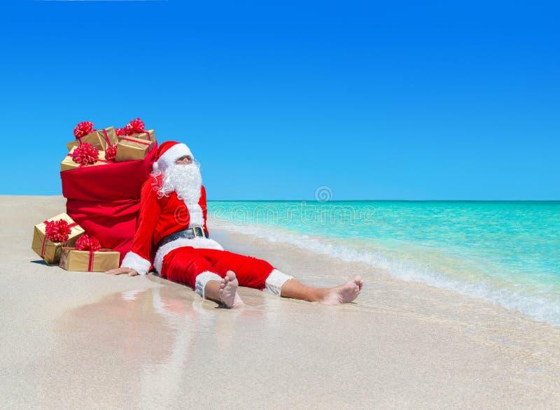 与礼物盒大袋的圣诞节圣诞老人在热带海滩 免版税库存图片