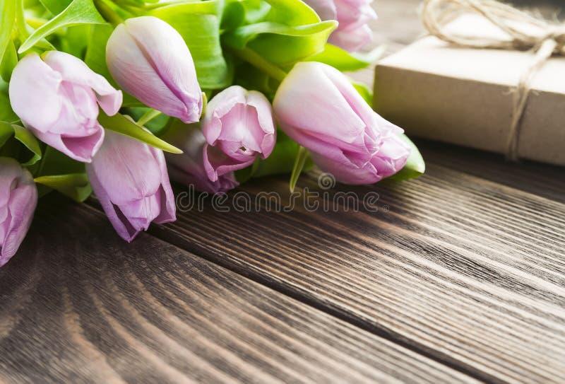 与礼物盒的春天紫色郁金香在桌上 免版税库存图片