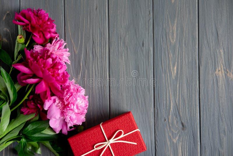与礼物盒的牡丹花在与地方的灰色木背景题字的 E 招呼用信件,招呼 库存照片