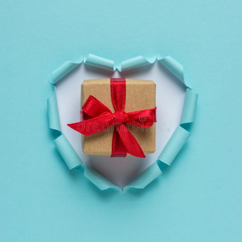 与礼物盒的生动的被撕毁的纸心脏在明亮的背景 库存图片