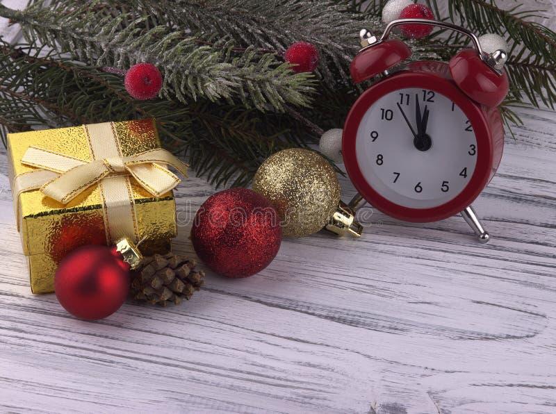 与礼物盒红色闹钟锥体自然冷杉的圣诞节装饰分支在白色木背景,关闭的金黄球  免版税库存照片