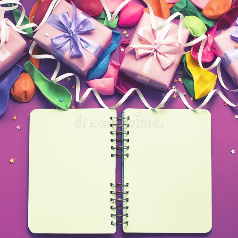 与礼物缎带弓可膨胀的球的装饰箱子构成蜿蜒紫色背景舱内甲板一张顶视图  免版税库存图片