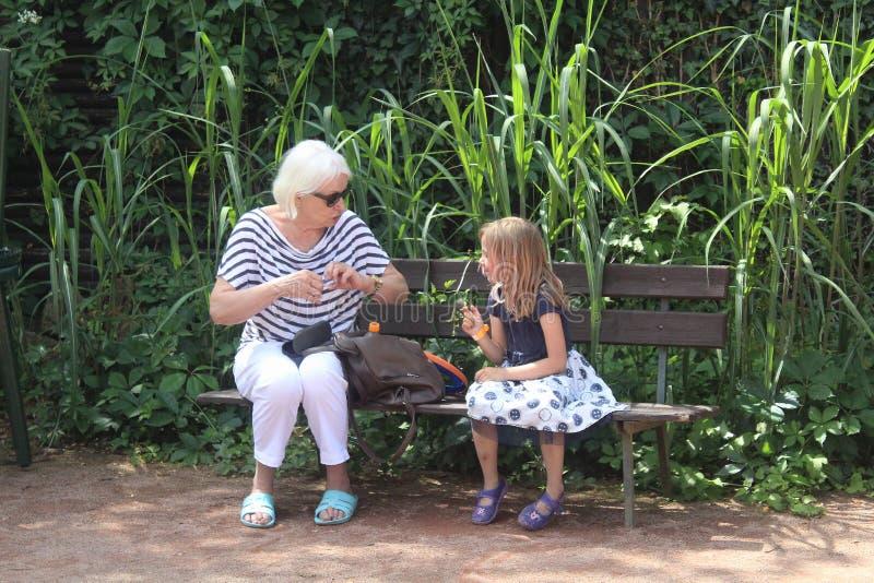 与祖母的下午-有她的祖母的小女孩公园的 免版税库存照片