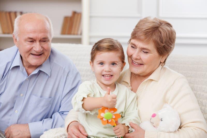 与祖父母的俏丽的孩子打手势 库存照片