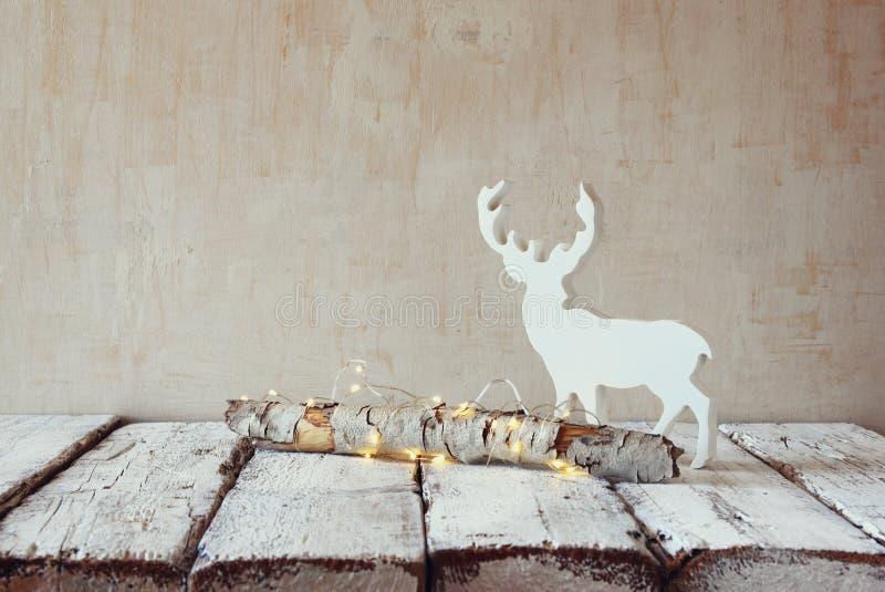 与神仙的圣诞灯和驯鹿的老树日志在木桌上 选择聚焦 库存照片