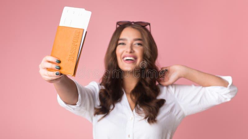 与票的快乐的女孩旅行家陈列护照到照相机 免版税库存图片