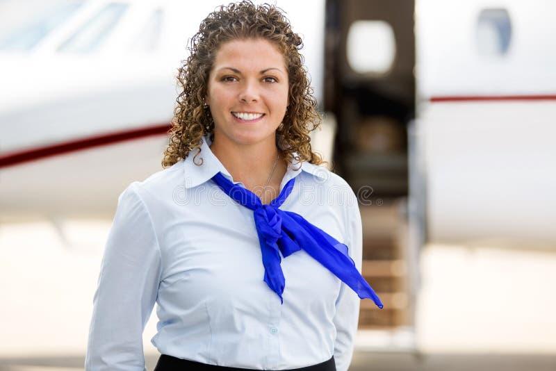 与私人喷气式飞机的美丽的空中小姐 免版税库存图片