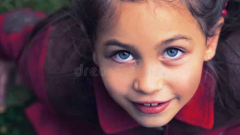 与秋叶的逗人喜爱的可爱的小孩女孩画象在背景的地面上 孩子室外在公园或森林 免版税库存图片
