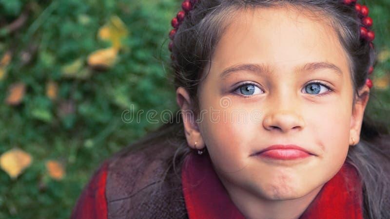 与秋叶的逗人喜爱的可爱的小孩女孩画象在背景的地面上 孩子室外在公园或森林 免版税库存照片