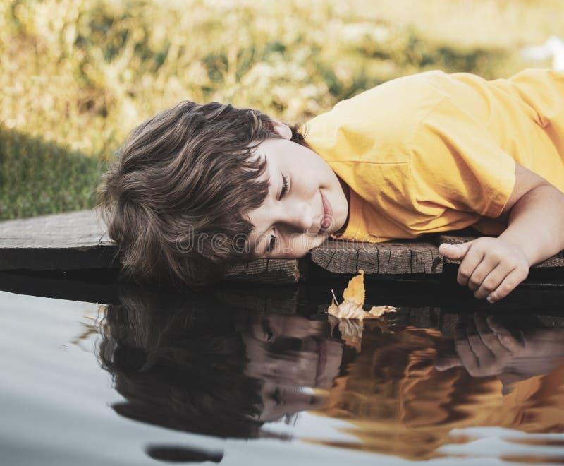 与秋天叶子船的男孩戏剧在水,公园戏剧的孩子中与叶子在河 免版税图库摄影