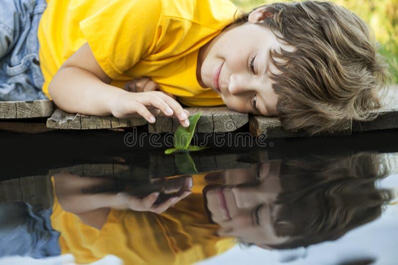 与秋天叶子船的男孩戏剧在水,孩子中在公园演奏w 库存图片