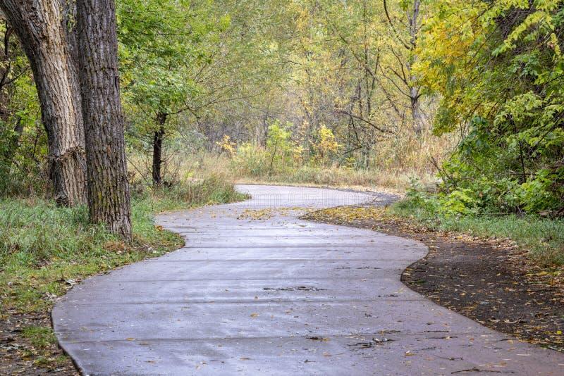 与秋天颜色的有风自行车足迹 库存照片