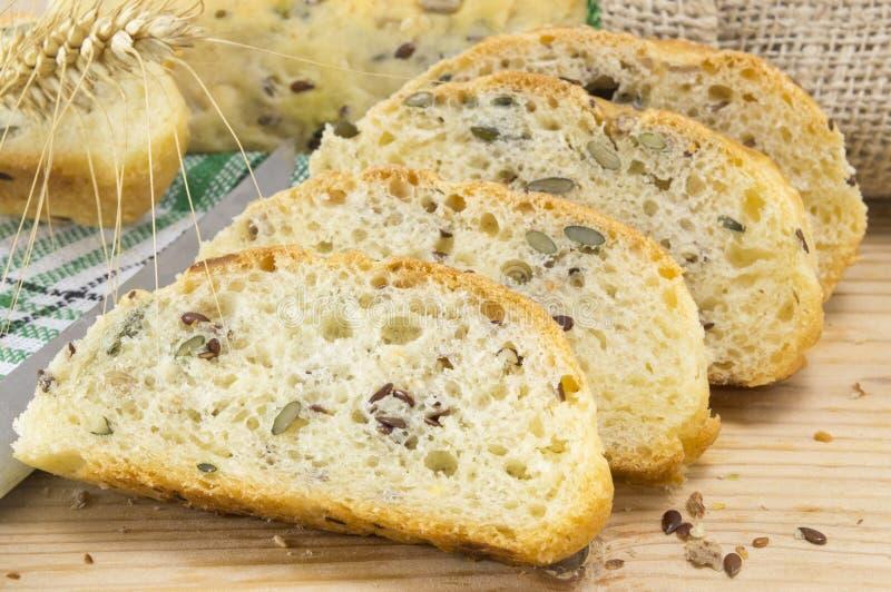 与种子的切的家制面包在桌上 免版税库存图片