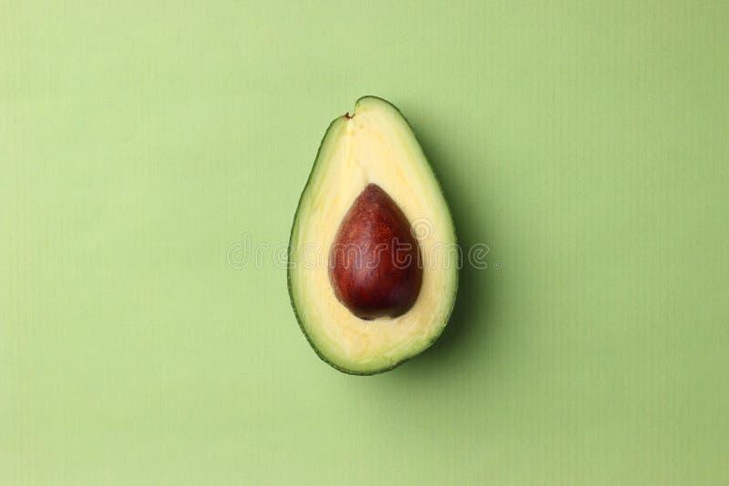 与种子的半鲕梨在一张绿色背景顶视图 库存照片