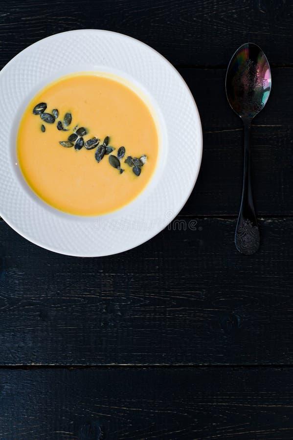 与种子的南瓜汤在黑背景的一块白色板材 免版税库存照片