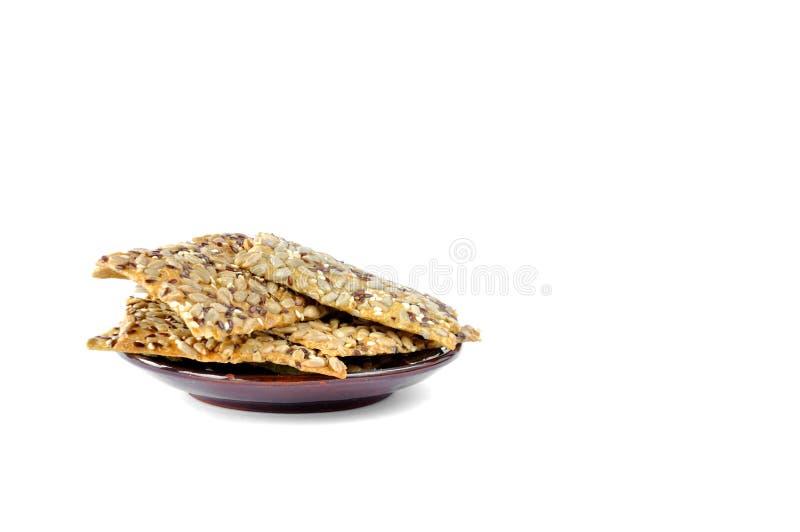 与种子的曲奇饼在白色背景的一块板材 图库摄影