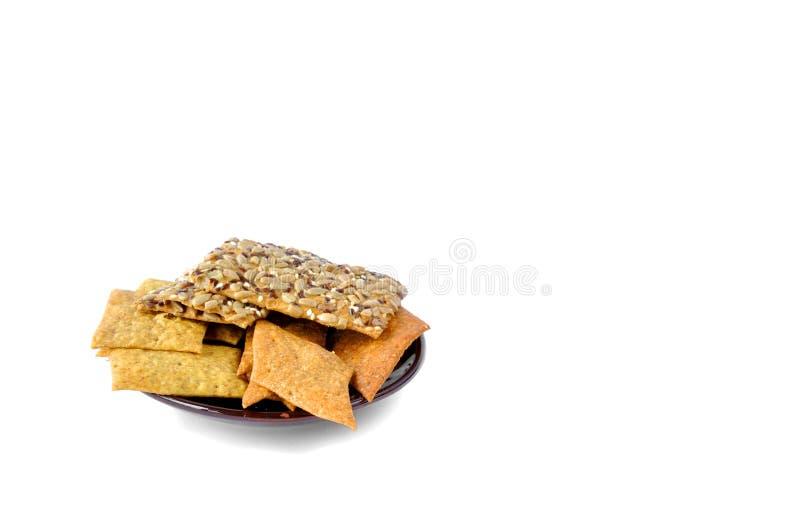 与种子的曲奇饼在白色背景的一块板材 库存照片