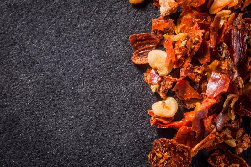 与种子的被捣的红辣椒在一个黑暗的背景特写镜头 免版税库存照片