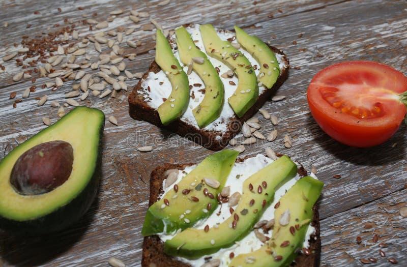 与种子的鲕梨多士在木葡萄酒背景 切片在全麦面包的鲕梨用向日葵和亚麻籽 免版税图库摄影