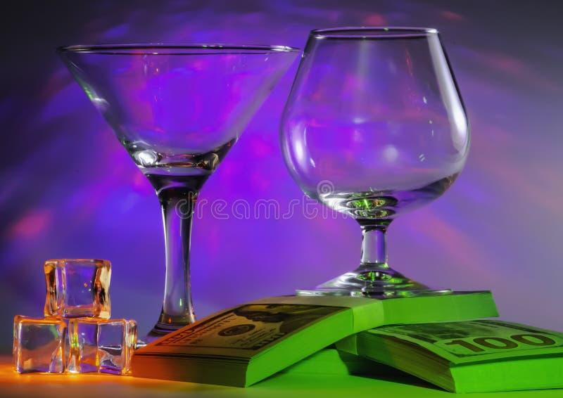 与科涅克白兰地玻璃一起的马蒂尼鸡尾酒玻璃在一盒100s美元和冰块与闪动的明亮的紫罗兰色光  免版税库存照片