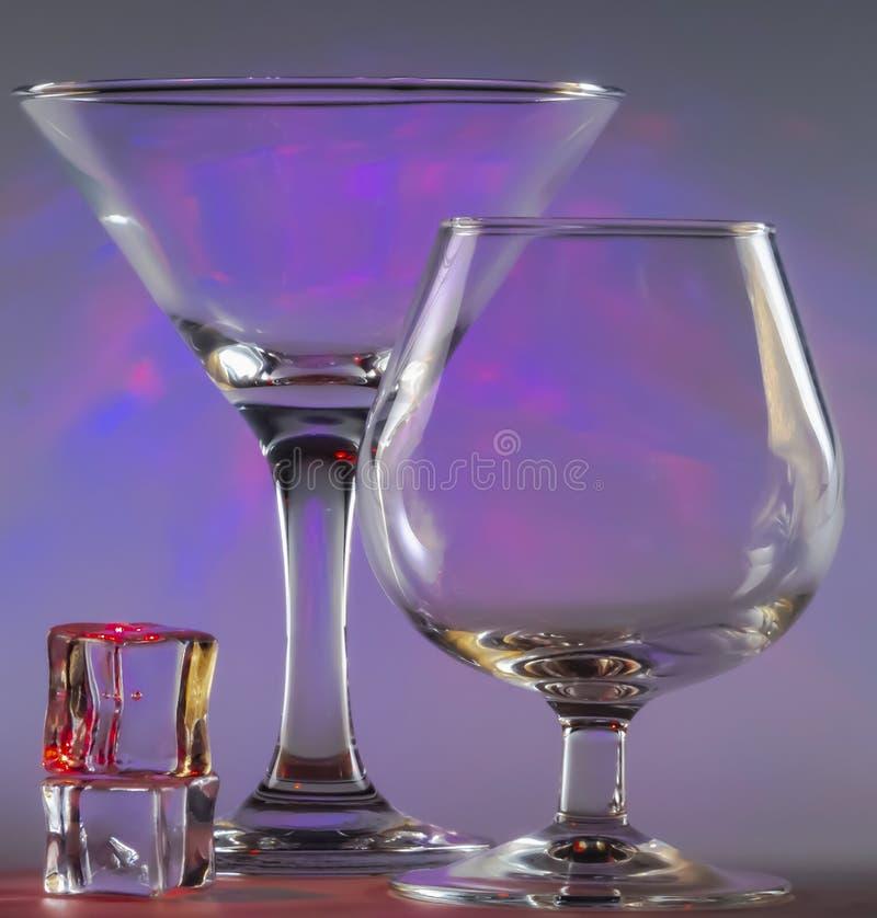与科涅克白兰地玻璃和冰块一起的马蒂尼鸡尾酒玻璃与在背景的闪动的光滑的紫罗兰色光 库存图片