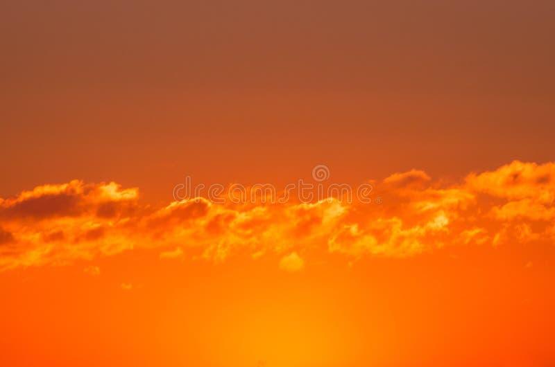 与积云一个均匀层的明亮的橙红日落  库存图片