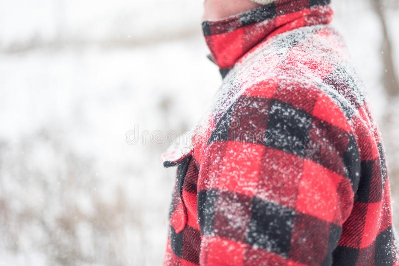 与积雪的人的冬天背景红色夹克的 图库摄影