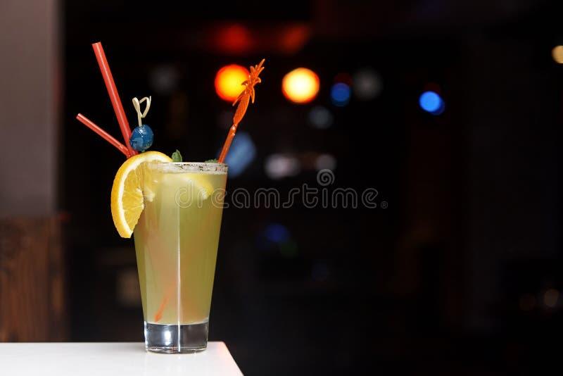 与秸杆和蓝色樱桃的冷的橙色鸡尾酒 免版税库存图片