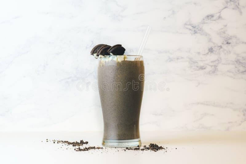与秸杆的巧克力饼干奶昔在与曲奇饼面包屑的高透明玻璃 库存照片