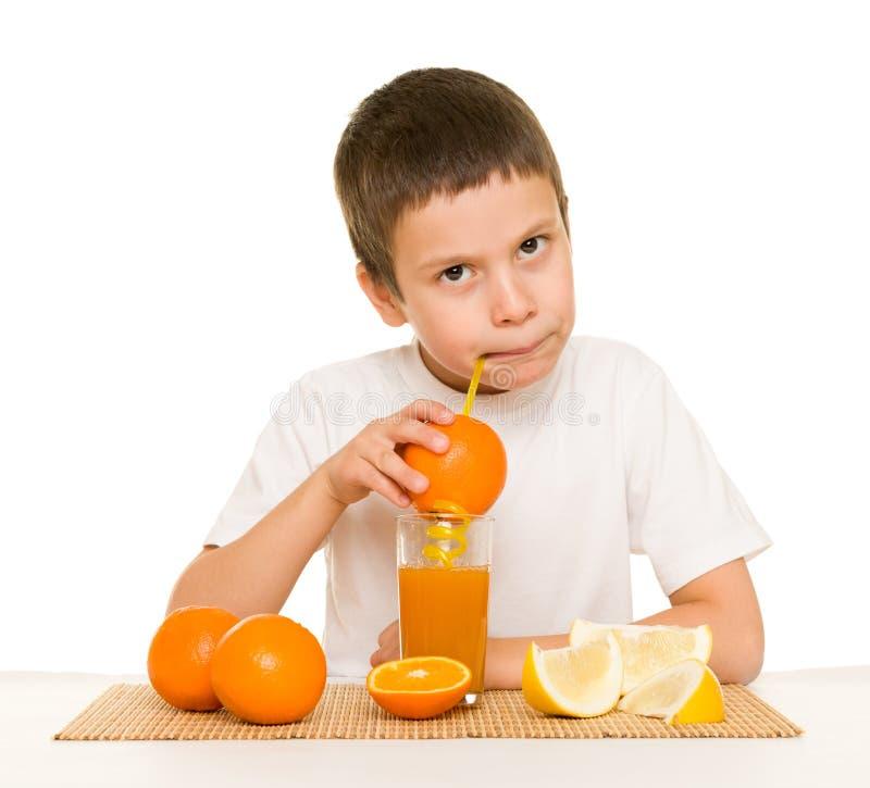 与秸杆的男孩饮料橙汁 免版税库存照片