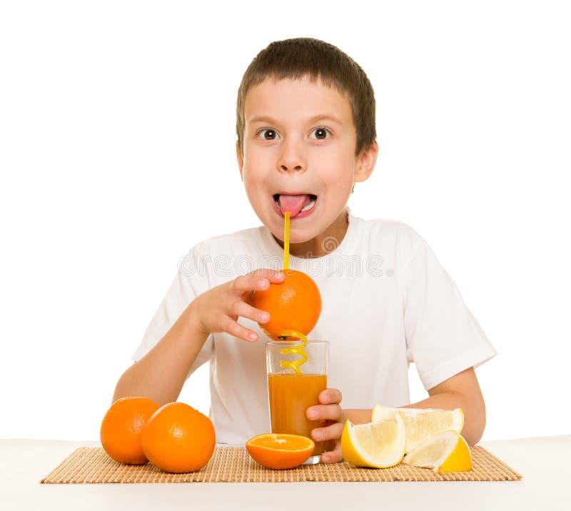 与秸杆的男孩饮料橙汁 免版税库存图片