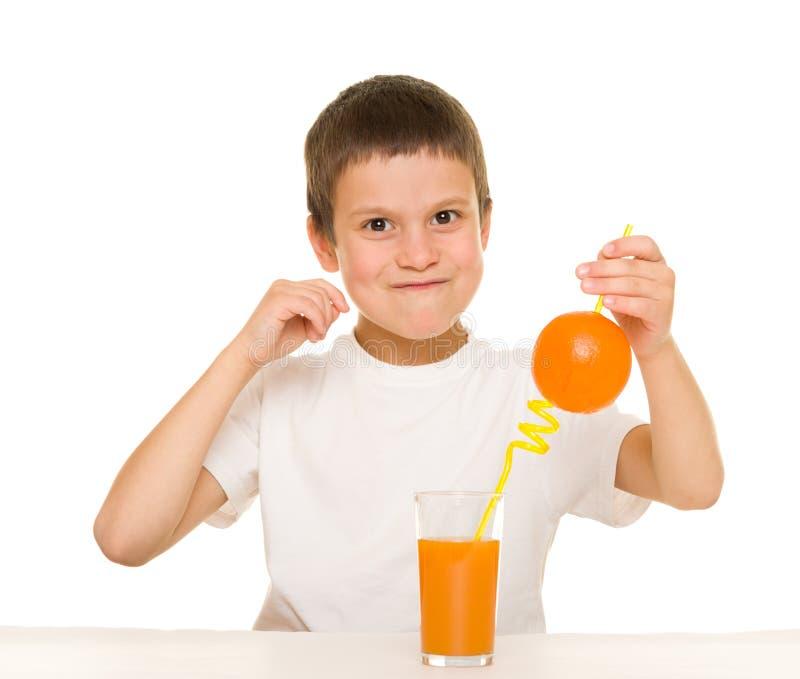 与秸杆的男孩饮料橙汁 免版税图库摄影