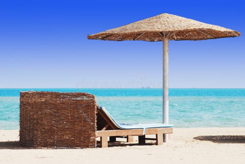 与秸杆遮光罩的海滩睡椅 库存照片