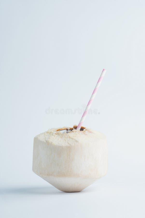 与秸杆里面的新近地被切的水多的椰子在白色背景 免版税库存图片