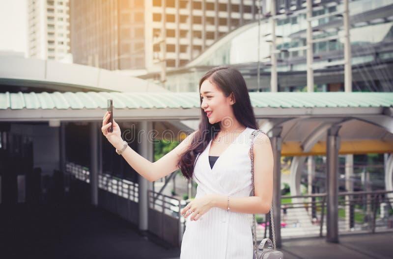 与移动电话的画象美好的亚洲妇女selfie和走在城市,愉快女性的信心和微笑,生活方式conce 库存照片