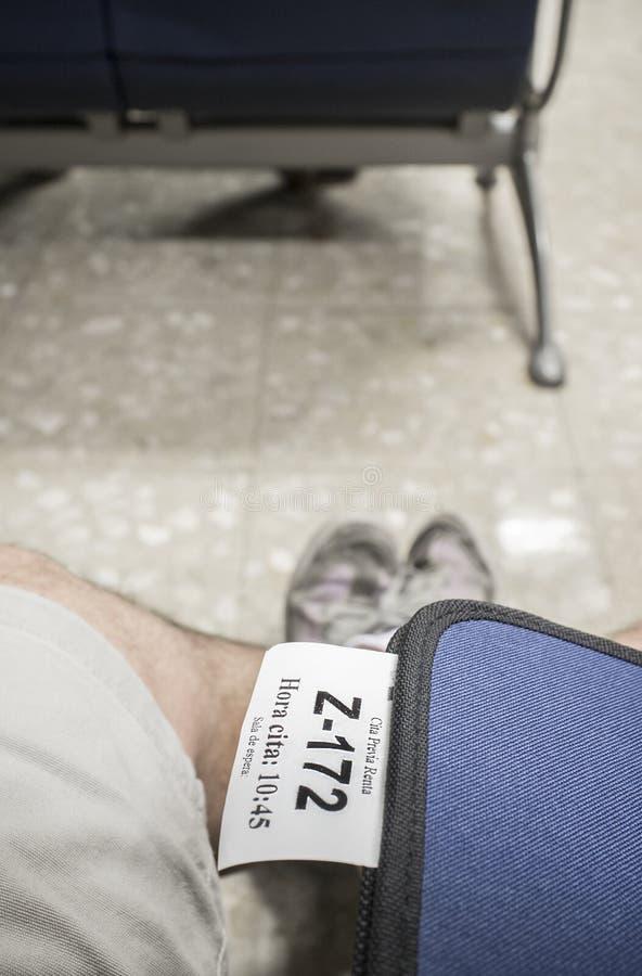 与税机构任命票的文件夹在休息室的男性腿 申报纳税概念 免版税库存照片