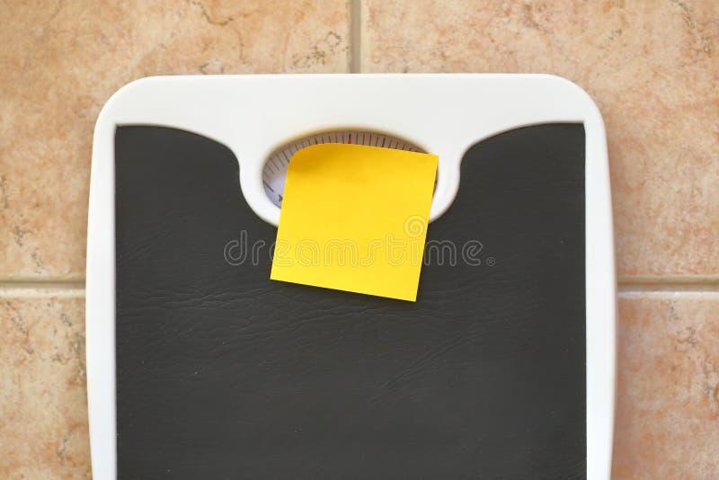 与空白的备忘录贴纸的体重计 图库摄影