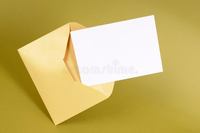 与空白的消息卡片的金信封 免版税库存照片