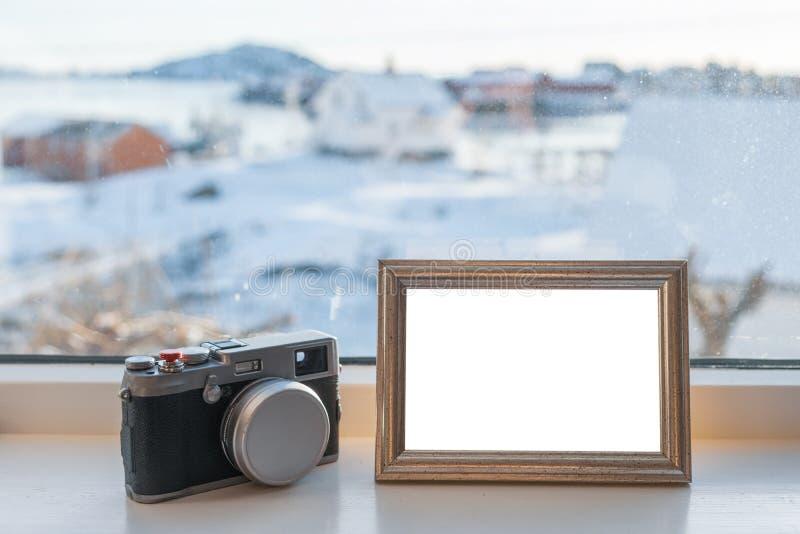 与空白的画框的葡萄酒照相机在窗口基石 免版税库存照片
