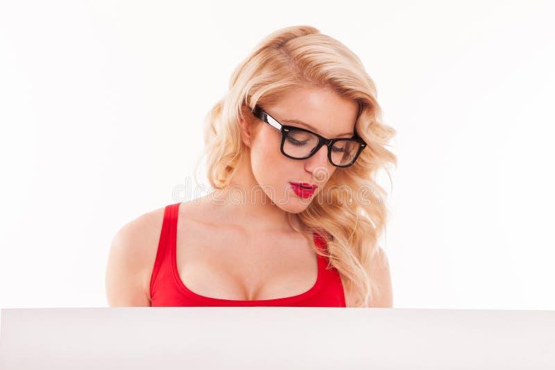 与空白的白板的肉欲的白肤金发的妇女画象。隔绝  免版税库存照片