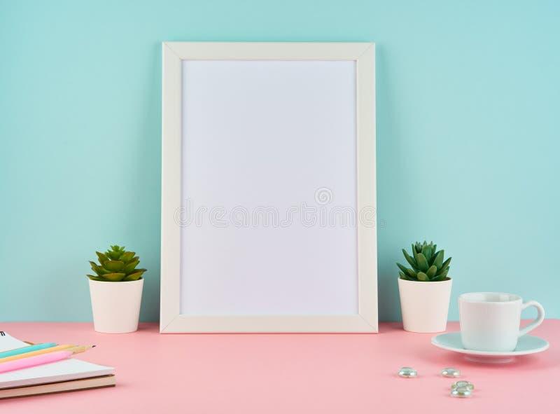 与空白的白色框架、植物仙人掌、咖啡或茶的大模型在桃红色桌上对有拷贝空间的蓝色墙壁 库存照片