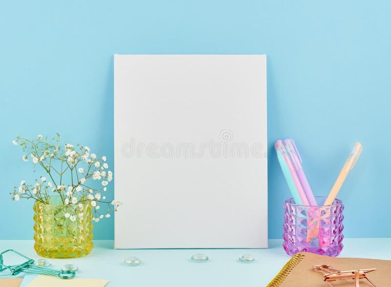 与空白的白色框架的大模型在蓝色桌上对蓝色墙壁,在vaze的花 图库摄影