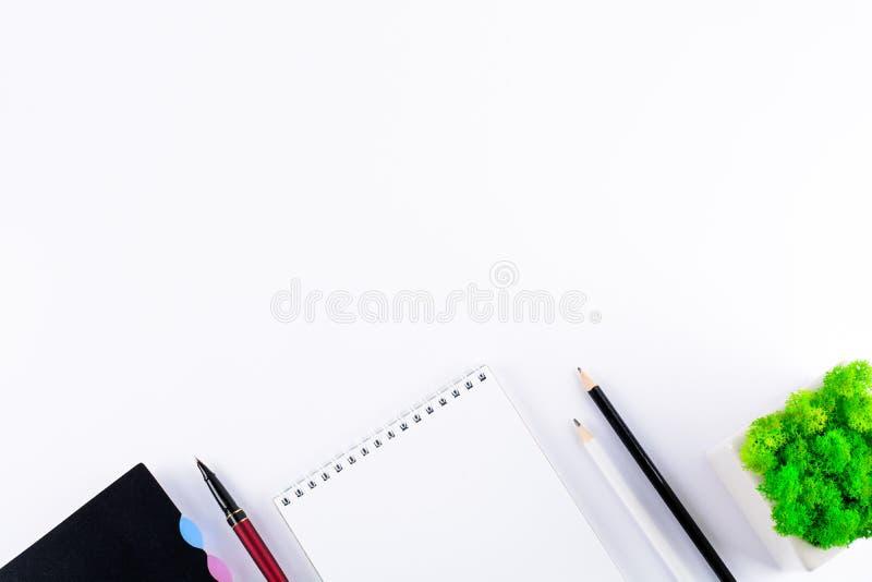 与空白的笔记本、巧妙的电话、耳机和其他办公用品的白色办公桌桌 顶视图 复制空间 平的位置 免版税库存照片