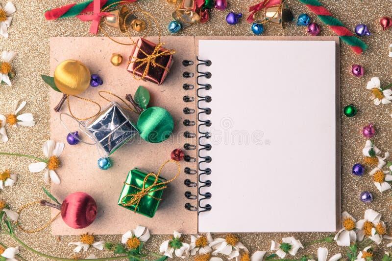 与空白的笔记本、礼物盒、雏菊花、糖果球和装饰的圣诞节和新年木背景横幅在葡萄酒 免版税库存图片