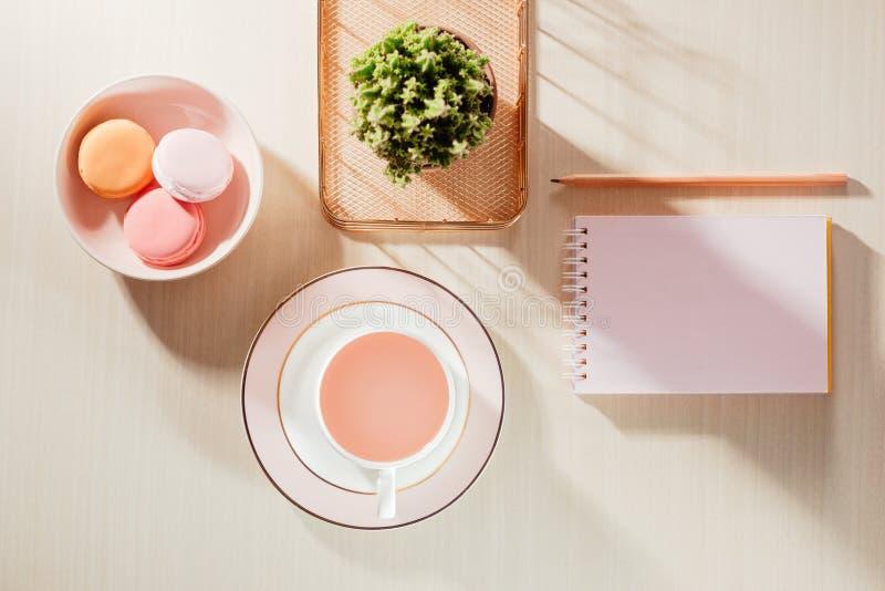 与空白的笔记本、蛋白杏仁饼干、供应和咖啡杯的被称呼的股票摄影米黄办公桌桌 免版税库存图片