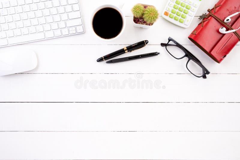 与空白的笔记本、键盘计算器、咖啡杯和其他办公用品的白色木办公桌桌 图库摄影