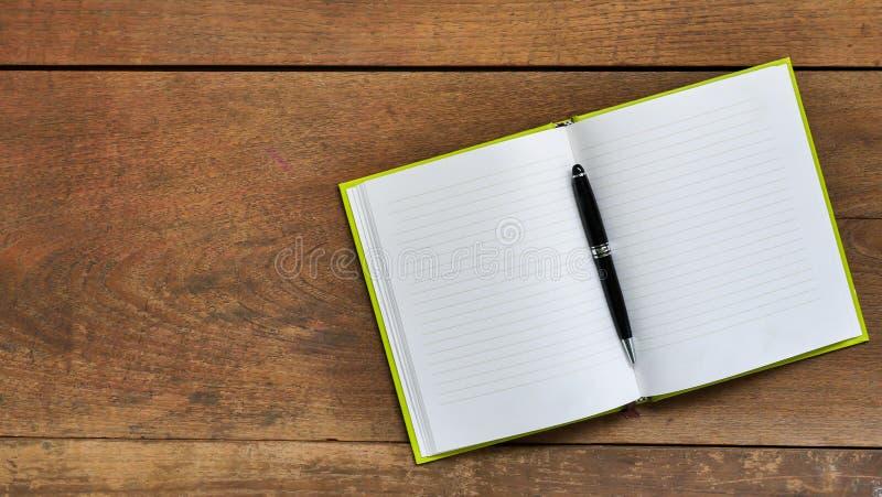 与空白的笔记本的顶视图在木桌b上的工作区和笔 库存图片