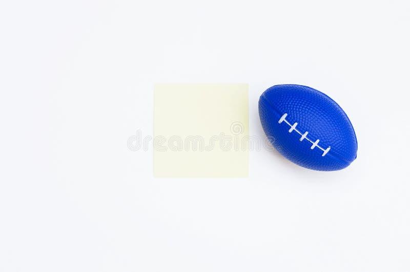 与空白的笔记的蓝色橄榄球形状按摩球关于白色背景 库存照片
