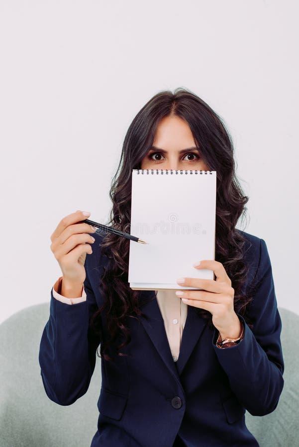与空白的笔记薄和指向的年轻女实业家覆盖物面孔 库存图片